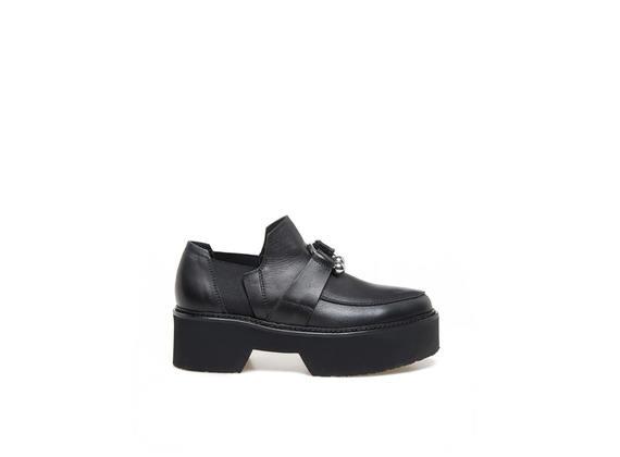 Mokassin aus schwarzem Leder mit Piercing und Maxisohle aus Gummi