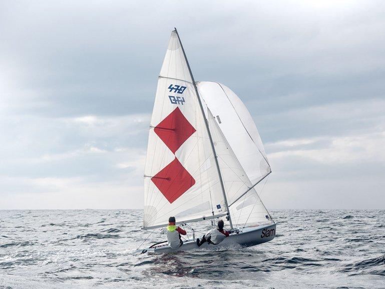 Deportistas de vela con prendas técnicas SLAM navegando en un barco de vela 470