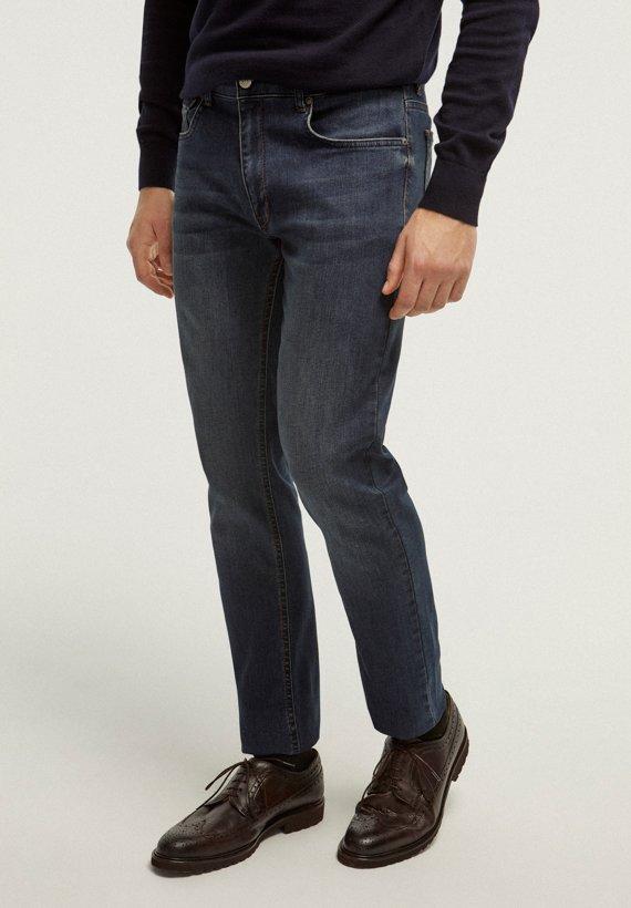 Vaquero oscuro semi-slim con detalle de la marca en bolsillo trasero