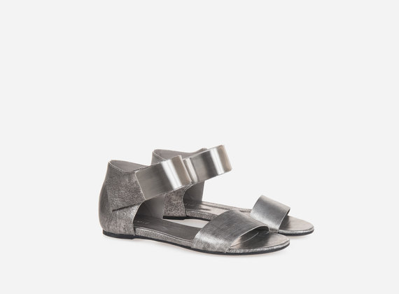 Laminated sandal with metal closing strap