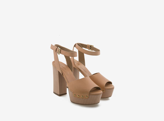 Wooden sandal with beige leather fastening