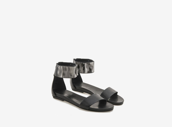 Black leather sandal with metallic plaque
