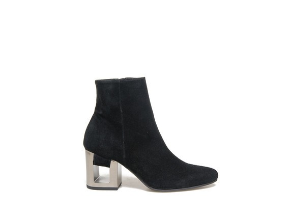 Ankle boot in black suede with band going through the perforated heel