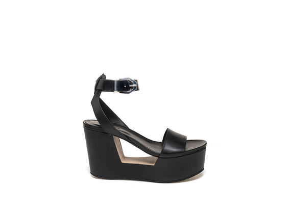 Sandal with buckle on perforated wedge