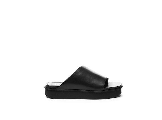 Black leather asymmetrical slipper on a flatform sole