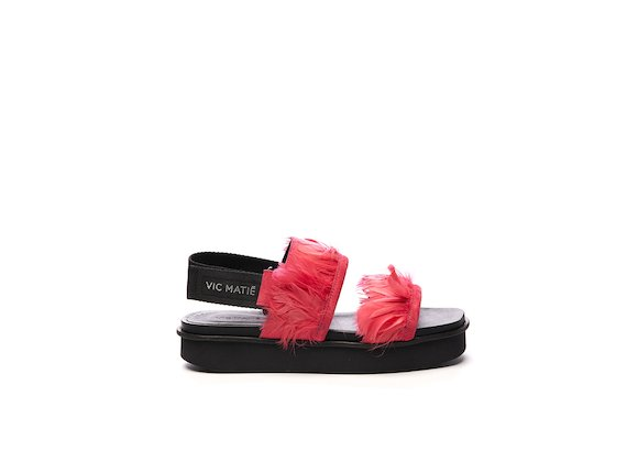 Sandal with fuchsia feather bands on a flatform sole