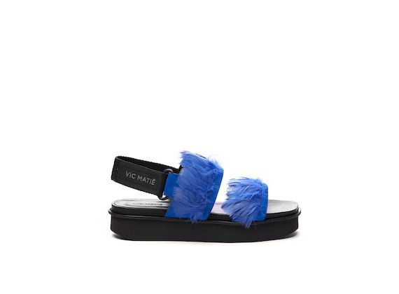 Sandal with cornflower blue feather bands on a flatform sole
