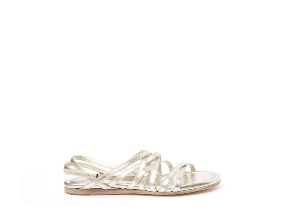 Flat sandal with thin gold cross-over bands