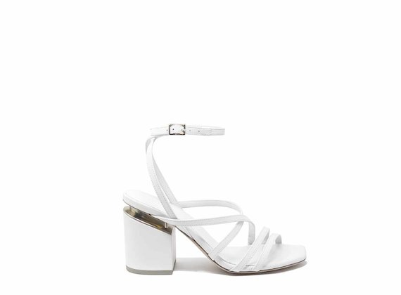 White sandals with criss-crossing strips and suspended heels