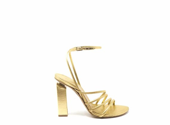 High-heeled sandals with golden strips and ankle strap