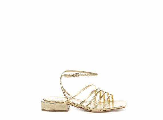 Sandales plates avec lanières et bride cheville dorées